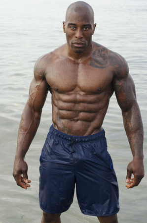 pecs: Black bodybuilder relaxing at the beach after a hard workout during a summer vacation. Strong man with perfect abs, pecs shoulders,biceps, triceps