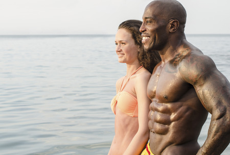perfect: Fit happy couple enjoying their vacation at the beach, a strong bodybuilder, black man and a white brunette woman