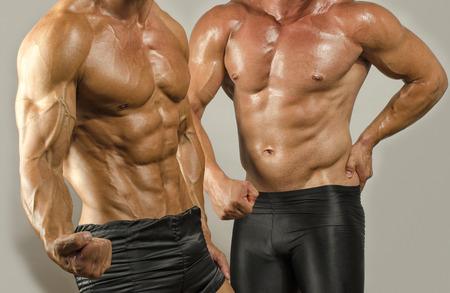 hombre fuerte: Carrocer�a apta contra la grasa corporal, flexionando los m�sculos. Dos hombres mostrando su b�ceps, abdominales, el pecho y los hombros en un concurso