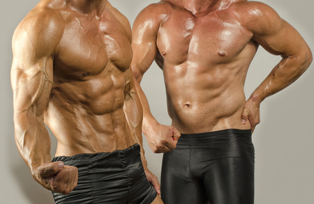 muscular man: Fit body versus fat body, flexing muscles. Two men showing their biceps,abs, chest and shoulders in a contest Stock Photo