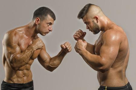 arts: Two muscular men fighting, bodybuilders punching each other, training in martial arts, boxing, jiu jitsu and mma