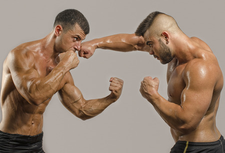 Two muscular men fighting, bodybuilders punching each other, training in martial arts, boxing, jiu jitsu and mma