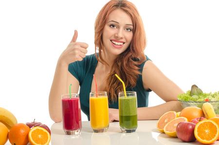 zumo verde: Mujer feliz que tiene una mesa llena de alimentos org�nicos, jugos y batido. Mujer joven alegre que come la ensalada sana y frutas. Aislado en blanco.