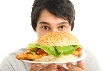 comida chatarra: El hombre que ofrece una gran hamburguesa, comida rápida, tomar hacia fuera para usted