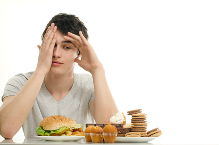 fatty food: Young man holding in front lots of cookies and a big hamburger. Choosing between chocolate, cupcakes, biscuits and a burger. Trying to get fat eating fast food and lots of sugar