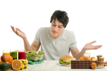 Man choosing between fruits, smoothie and organic healthy food against sweets, sugar, lots of candies and a big hamburger, fast food