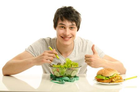 Hombre joven que sostiene delante un plato de ensalada y una hamburguesa grande. La elección entre el bien y el mal la comida sana de alimentos poco saludables. Los alimentos ecológicos frente a la comida rápida