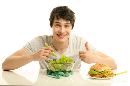 Young man holding in front a bowl of salad and a big hamburger. Choosing between good healthy food and bad unhealthy food. Organic food versus fast food