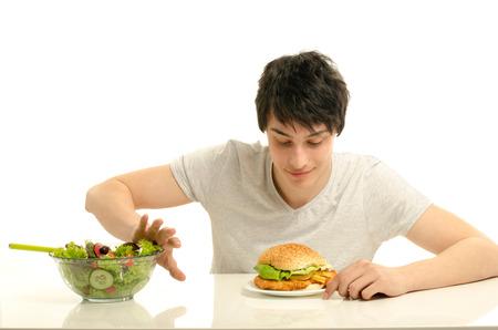 Young man holding in front a bowl of salad and a big hamburger. Choosing between good healthy food and bad unhealthy food. Organic food versus fast food