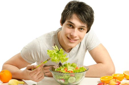 frutas divertidas: Hombre que tiene una mesa llena de alimentos orgánicos, jugos y batido. Alegre joven comiendo una ensalada saludable y frutas, la dieta