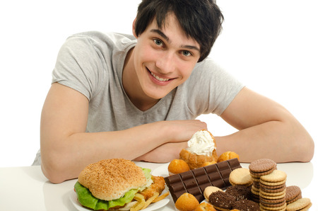 Young man holding in front lots of cookies and a big hamburger. Choosing between chocolate, cupcakes, biscuits and a burger. Trying to get fat eating fast food and lots of sugar