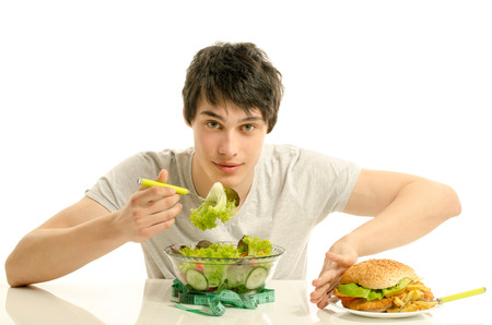 unhealthy food: Young man holding in front a bowl of salad and a big hamburger. Choosing between good healthy food and bad unhealthy food. Organic food versus fast food
