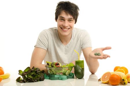 Man choosing between eating healthy organic food and pills. Happy man having a table full of organic food,juices and smoothie. Eating green food and taking spirulina pills