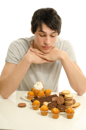 withhold: Man in love with sweets, candies,chocolate and sugar but trying to withhold. Forbidden sweets for a healthy longer life, throwing up to stay slim Stock Photo