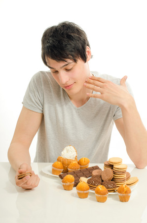 forbidden love: Man in love with sweets, candies,chocolate and sugar but trying to withhold. Forbidden sweets for a healthy longer life, throwing up to stay slim Stock Photo