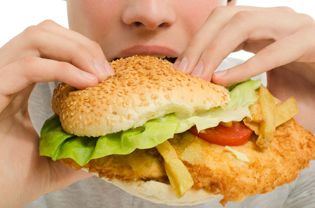 Close up of a man eating a big hamburger, fast food unhealthy burger