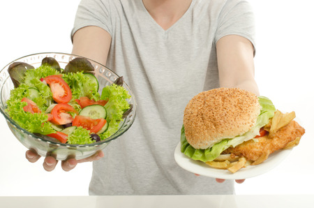 Man offering you a salad and a hamburger. Young man holding in front a bowl of salad and a big burger. Choosing between good healthy food and bad unhealthy food. Fast food versus organic