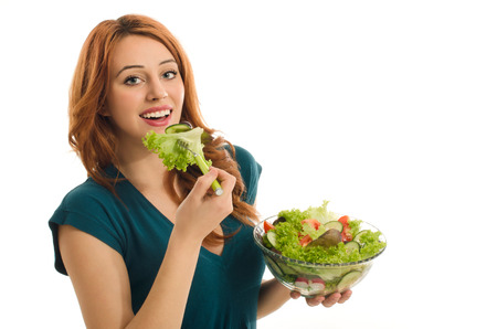approving: Happy woman eating salad. Woman keeping a diet with green salad and approving organic raw food