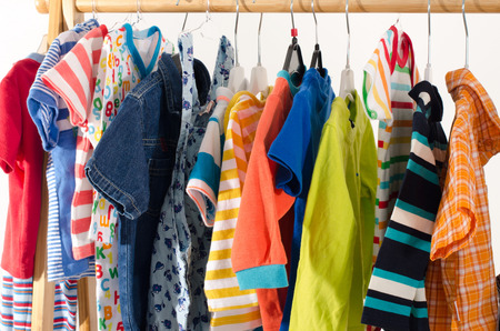 apparel: Dressing closet with clothes arranged on hangers.Colorful wardrobe of newborn,kids, toddlers, babies full of all clothes.Many t-shirts,pants, shirts,blouses, onesie hanging Stock Photo