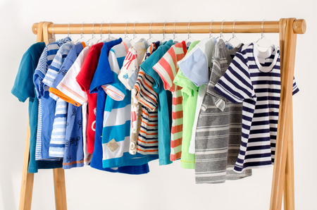 closet: Dressing closet with clothes arranged on hangers.Colorful wardrobe of newborn,kids, toddlers, babies full of all clothes.Many t-shirts,pants, shirts,blouses, onesie hanging Stock Photo
