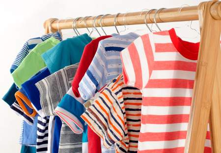 baby wardrobe: Dressing closet with clothes arranged on hangers.Colorful wardrobe of newborn,kids, toddlers, babies full of all clothes.Many t-shirts,pants, shirts,blouses, onesie hanging Stock Photo
