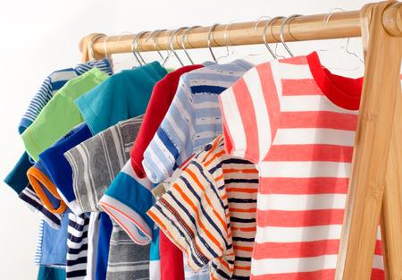 ropa colgada: Vestir armario con ropa dispuestas en hangers.Colorful armario de reci�n nacidos, ni�os, ni�os, beb�s llenos de toda clothes.Many camisetas, pantalones, camisas, blusas, onesie colgante