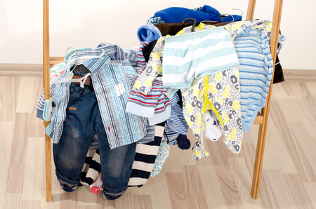 Wardrobe of newborn,kids, toddlers, babies.Many t-shirts,pants, shirts, shoes, hat,blouses, onesie in a pile . Messy clothes thrown on a shelf