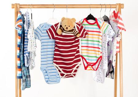 Dressing placard avec des vêtements disposés sur onesie hangers.Colorful des nouveau-nés, enfants en bas âge, les bébés sur une rack.Many coloré t-shirts, chemises, chemisiers, onesie pendaison, jouet ours