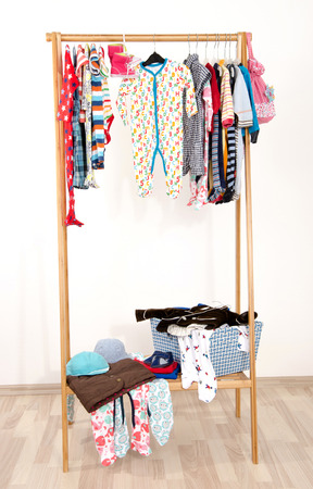 messy clothes: Dressing closet with clothes arranged on hangers.Colorful wardrobe of newborn,kids, toddlers, babies on a rack.Many t-shirts,pants, shirts,blouses, onesie hanging. Messy clothes thrown on a shelf