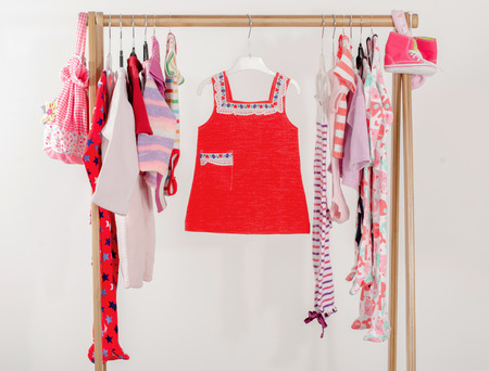 girl in red dress: Dressing closet with clothes arranged on hangers.Red wardrobe of newborn,kids, toddlers, babies on a rack.Many t-shirts,pants, shirts,blouses, onesie hanging, little girl red dress Stock Photo