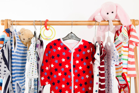 blouses: Dressing closet with clothes arranged on hangers.Colorful wardrobe of newborn,kids, toddlers, babies full of all clothes.Many t-shirts,pants, shirts,blouses, onesie hanging, bear and rabbit toy