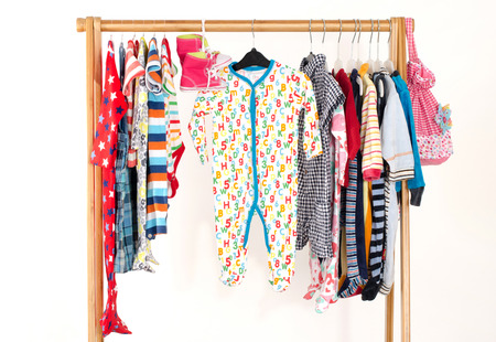 blouses: Dressing closet with clothes arranged on hangers.Colorful wardrobe of newborn,kids, toddlers, babies full of all clothes.Many t-shirts,pants, shirts,blouses,yellow hat,shoes, onesie hanging