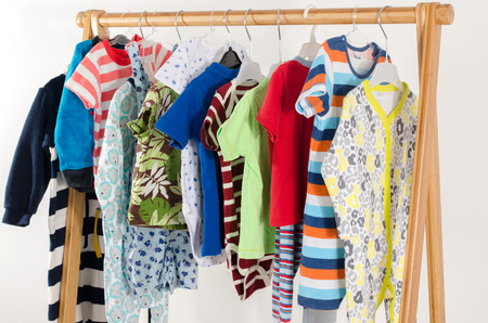 blouses: Dressing closet with clothes arranged on hangers.Colorful wardrobe of newborn,kids, toddlers, babies full of all clothes.Many t-shirts,pants, shirts,blouses, onesie hanging Stock Photo