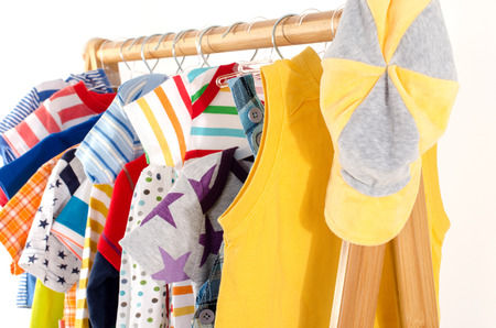 blouses: Dressing closet with clothes arranged on hangers.Colorful wardrobe of newborn,kids, toddlers, babies full of all clothes.Many t-shirts,pants, shirts,blouses,yellow hat, onesie hanging