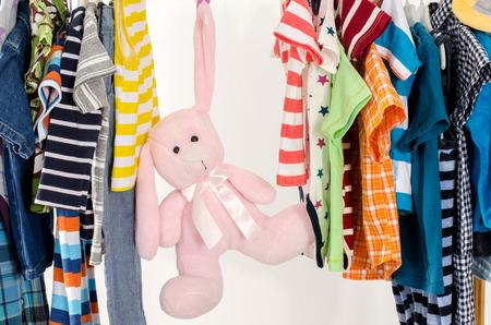 moda ropa: Closet vestidor con ropa dispuestas en hangers.Colorful armario de recién nacidos, niños, bebés, niños pequeños llenos de toda clothes.Many camisetas, pantalones, camisas, blusas, onesie en un estante, conejo rosado del juguete que cuelga
