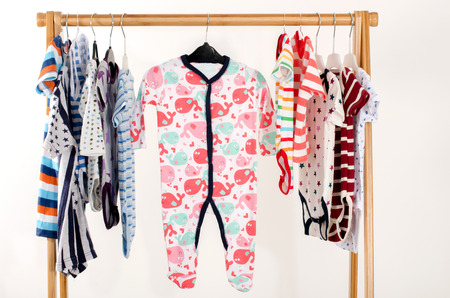 fashion clothing: Dressing closet with clothes arranged on hangers.Colorful onesie of newborn,kids, toddlers, babies on a rack.Many colorful t-shirts, shirts,blouses, onesie hanging