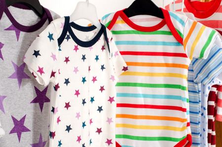 baby wardrobe: Dressing closet with clothes arranged on hangers.Colorful onesie of newborn,kids, toddlers, babies on a rack.Many colorful t-shirts, shirts,blouses, onesie hanging