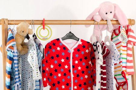 baby wardrobe: Dressing closet with clothes arranged on hangers.Colorful wardrobe of newborn,kids, toddlers, babies full of all clothes.Many t-shirts,pants, shirts,blouses, onesie hanging, bear and rabbit toy