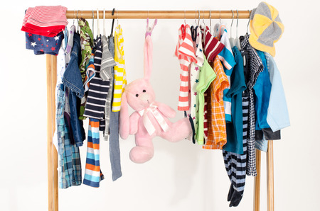 kids toys: Dressing closet with clothes arranged on hangers.Colorful wardrobe of newborn,kids, toddlers, babies full of all clothes.Many t-shirts,pants, shirts,blouses, onesie on a rack, pink rabbit toy hanging