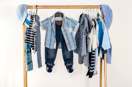 baby wardrobe: Dressing closet with clothes arranged on hangers.Blue and white wardrobe of newborn,kids, toddlers, babies full of all clothes.Many t-shirts,pants, shirts,blouses,blue hat, onesie hanging Stock Photo