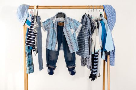 Dressing kast met kleren gerangschikt op hangers.Blue en wit garderobe van pasgeboren, kind, peuters, baby's vol van alle clothes.Many t-shirts, broeken, shirts, blouses, blauwe hoed, onesie hangende