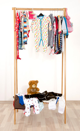 Dressing closet with clothes arranged on hangers.Colorful wardrobe of newborn,kids, toddlers, babies on a rack.Many t-shirts,pants, shirts,blouses, onesie hanging. Messy clothes thrown on a shelf