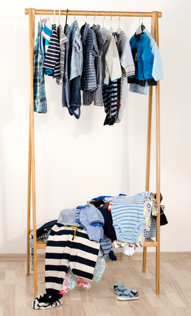 messy clothes: Dressing closet with clothes arranged on hangers.Wardrobe of newborn,kids, toddlers, babies.Many t-shirts,pants, shirts,blouses, shoes, onesie hanging. Messy clothes thrown on a shelf