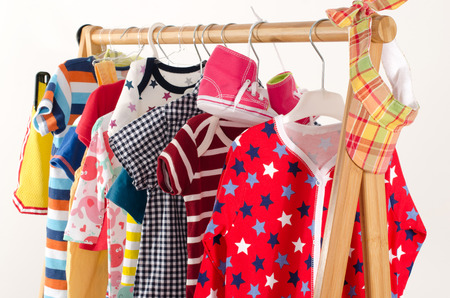 Dressing closet with clothes arranged on hangers.Colorful wardrobe of newborn,kids, toddlers, babies full of all clothes.Many t-shirts,pants, shirts,blouses,yellow hat,shoes, onesie hanging