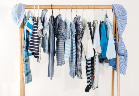 blouses: Dressing closet with clothes arranged on hangers.Blue and white wardrobe of newborn,kids, toddlers, babies full of all clothes.Many t-shirts,pants, shirts,blouses,blue hat, onesie hanging Stock Photo