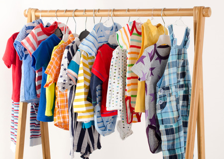 onesie: Dressing closet with clothes arranged on hangers.Colorful wardrobe of newborn,kids, toddlers, babies full of all clothes.Many t-shirts,pants, shirts,blouses, onesie hanging Stock Photo