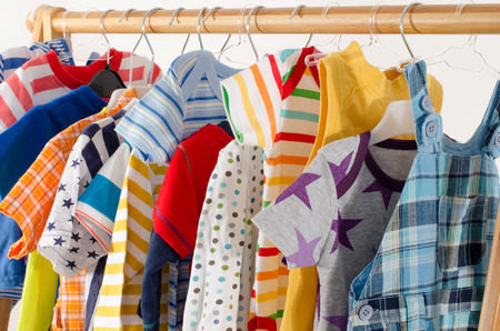 rack arrangement: Dressing closet with clothes arranged on hangers.Colorful wardrobe of newborn,kids, toddlers, babies full of all clothes.Many t-shirts,pants, shirts,blouses, onesie hanging Stock Photo