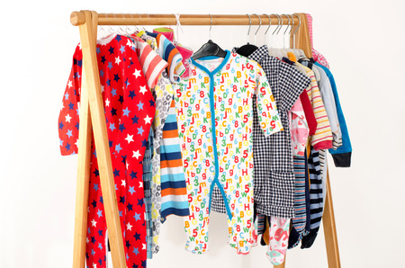 recien nacido: Vestir armario con ropa dispuestas en hangers.Colorful armario de recién nacidos, niños, niños, bebés llenos de toda clothes.Many camisetas, pantalones, camisas, blusas, sombrero amarillo, zapatos, onesie colgante