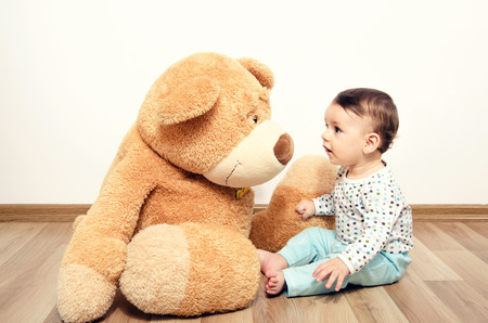 Beautiful innocent newborn speaking with his best friend, teddy bear. Adorable baby playing, having fun with his bear toy. Little sweet kid talking and listening his toy