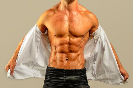topless: Gros plan sur abdos parfaits. Forte bodybuilder Topless avec six pack, entra�neur personnel v�tu d'une chemise blanche fl�chissant ses muscles